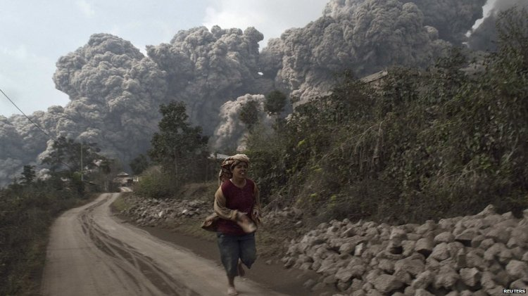 A local villager runs from the eruption of Sinabung volcano in Indonesia. Image credit: BBC News.